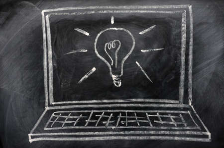 Chalk drawing of Laptop with a light bulb on the blackboard photo