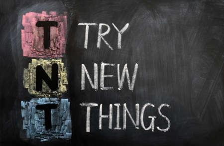 Acrónimo de TNT para la Prueba cosas nuevas escritas con tiza en una pizarra