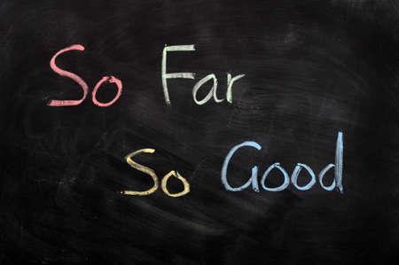 so: So far So good written in chalk on a blackboard Stock Photo