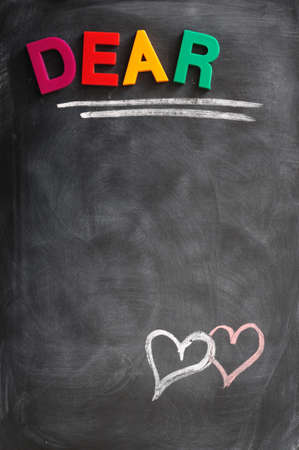 dear: Word of Dear with two hearts drawn with chalk on a blackboard