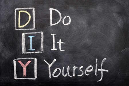 zelf doen: Acroniem van DIY voor Doe Het Zelf geschreven met krijt op een schoolbord Stockfoto