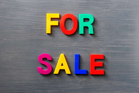 Words of For sale made of colorful letters on a gray board Stock Photo - 12389655