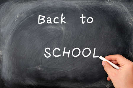 Back to school written on a blackboard with white chalk photo