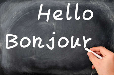 bonjour: Hello with French Bonjour written on a blackboard background with a hand holding chalk Stock Photo