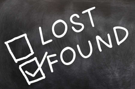 found: Lost and found check boxes with found checked, written with chalk on a blackboard Stock Photo