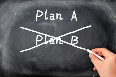 Plan A and Plan B written on a blackboard background with a hand holding chalk photo