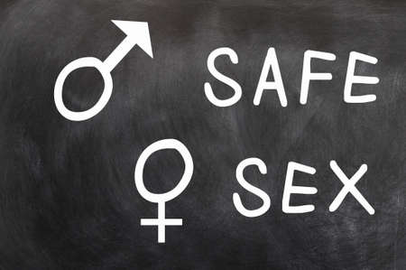 sex education: Safe Sex with gender symbols written with chalk on a blackboard Stock Photo