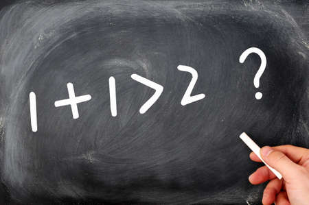 greater: One plus one is greater than two  Question written on a blackboard  Stock Photo