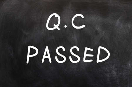 qc: QC passed written with chalk on a chalkboard  Stock Photo
