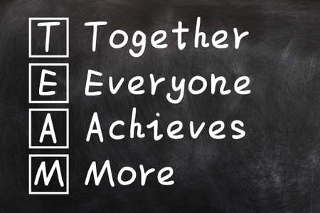 achieves: Acronym of TEAM for Together everyone achieves more written on a blackboard Stock Photo