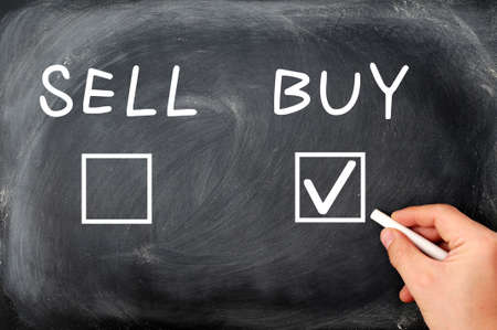 Buy or sell check boxes on a blackboard  Finance, economy, stock or real estate concept - time to buy   photo