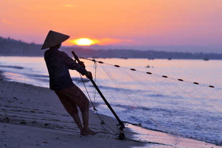 Silhouette of a fisherman on beach at sunrise Standard-Bild