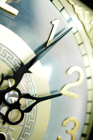Closeup view of an antique clock with black hands photo