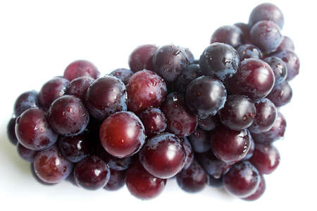 A cluster of ripe purple grapes on a white background Stock Photo