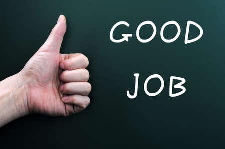 good job: Thumb up with  good job  written on a blackboard