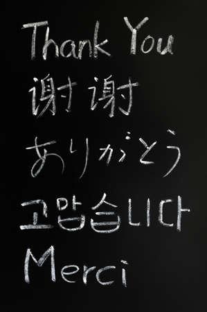 gratitudine: Grazie mille scritto con il gesso in varie lingue su una lavagna