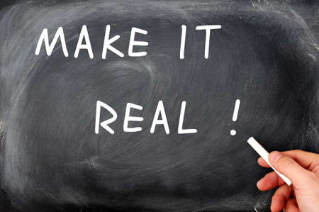 Make it real written on a blackboard - with a hand holding chalk photo