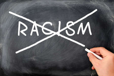 Crossing out racism on a blackboard, with a hand holding chalk photo