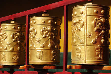 Golden Tibetan prayer wheels in a lamasery photo