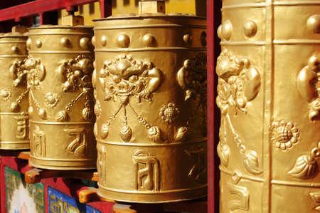 Golden Tibetan prayer wheels in a lamasery photo
