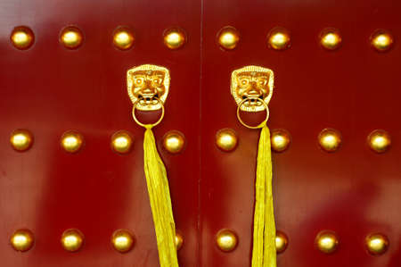 Traditional Chinese ancient red door with golden doorknobs photo
