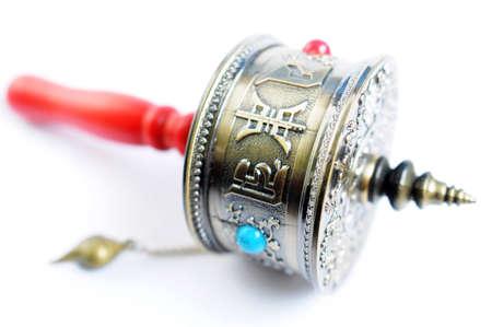 Closeup of a Tibetan prayer wheel on a white background photo