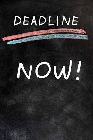 Deadline Now written with chalk on a blackboard  photo
