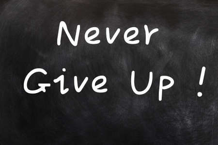 Never give up - words written in chalk on a blackboard  photo
