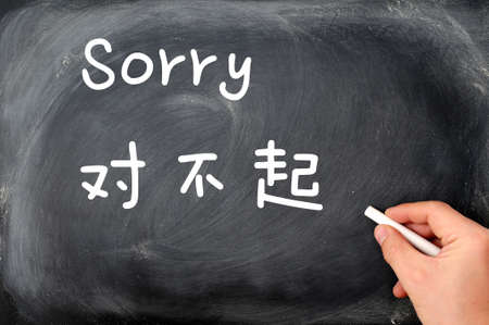 'Sorry' written on a blackboard background with a Chinese version, with a hand holding chalk. photo