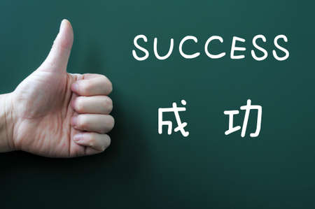 Success written on a blackboard with a Chinese version and with thumb up photo