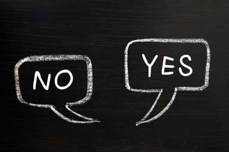 Two speech bubbles drawn with chalk on a blackboard for Yes and No Stock Photo