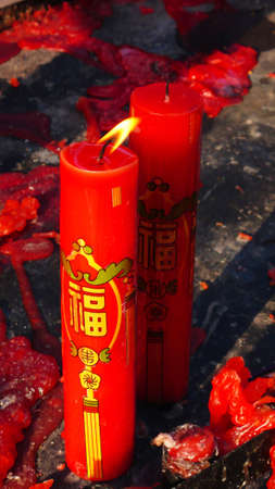 Red prayer candles burning in a buddhist temple photo