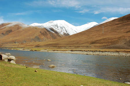 Landscape of snow-capped mountains and a river in the highland of Tibet