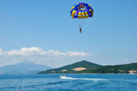 hang up: Scenery of paragliding high above the sea with mountains and skies as backgrounds  Stock Photo
