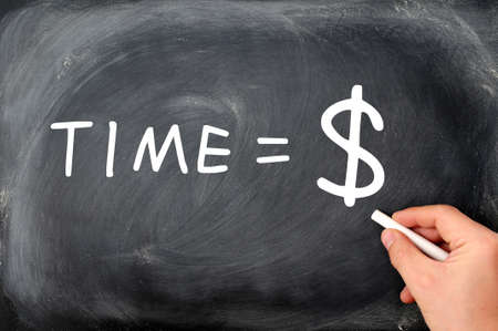 Time is money  handwritten with white chalk on a blackboard,with a hand holding chalk  photo