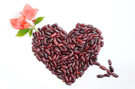 Heart shape with an arrow made of beans and flowers on a white background photo