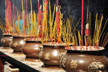 joss: Incense or joss sticks burning in jars in a temple