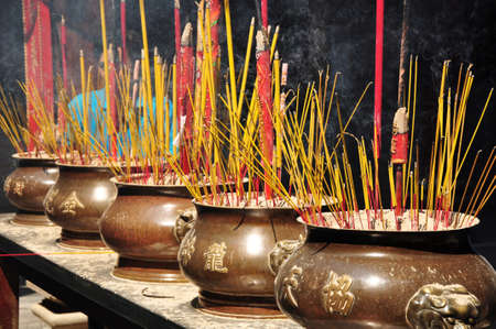 Incense or joss sticks burning in jars in a temple