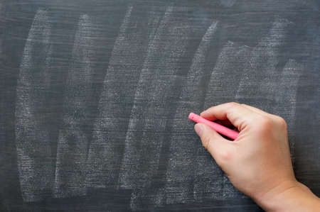 hand writing: Blank blackboard  chalkboard. Hand writing on green chalk board holding red chalk. Great texture for text.