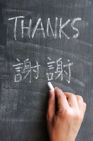 Thanks - word written on a blackboard with Chinese version characters, with a hand holding chalk. Standard-Bild