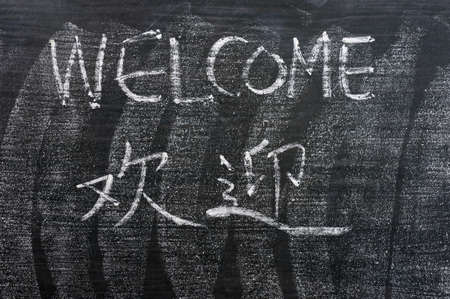 Welcome - word written on a blackboard with a Chinese translation photo