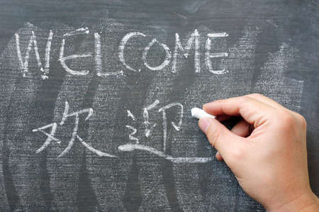 Welcome - word written on a blackboard with a Chinese translation, with a hand holding chalk photo
