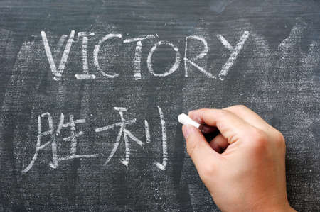 Victory - word written on a blackboard with a Chinese translation, with a hand holding chalk photo