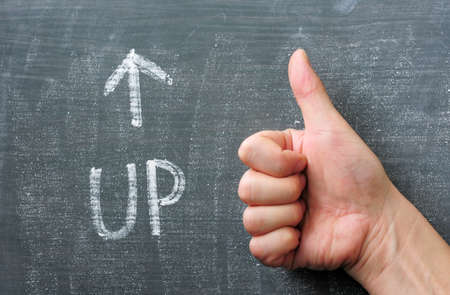 Up - word written on a blackboard with an arrow and thumb up gesture photo
