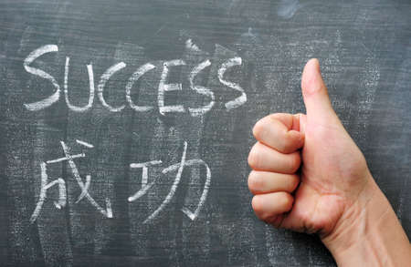 grundge: Success - word written with chalk on a blackboard with a Chinese translation Stock Photo