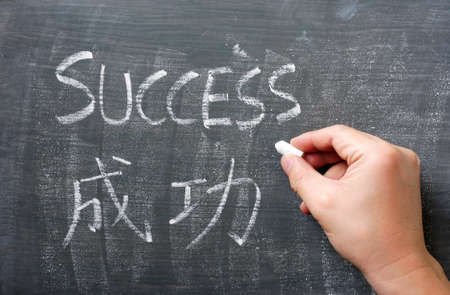 Success - word written with chalk on a blackboard with a Chinese translation, with a hand holding chalk photo