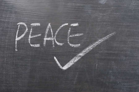 Peace - wrod written on a smudged blackboard with a tick photo