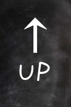 Up - word written on a blackboard with an arrow photo