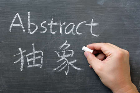 Abstract - word written on a blackboard with a Chinese translation, with a hand holding chalk photo