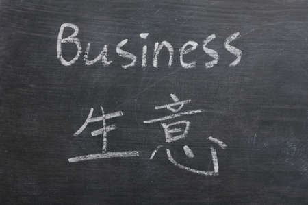 bilingual: Business- word written on a smudged blackboard with a Chinese translation